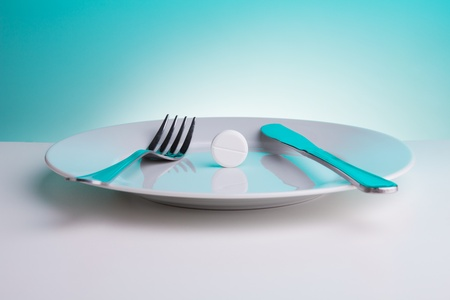 Medicine for digestion concept with plate with big white tablet and for and table knife photo