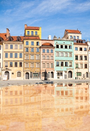 polska monument: Reflecting surface of fountain and Warsaw old town marketplace square and colorful houses