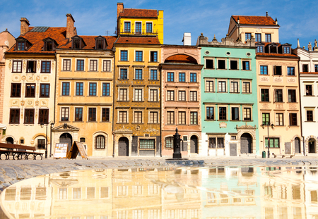 polska monument: Reflecting surface of fountain and Warsaw, Poland old town marketplace square and colorful houses Stock Photo