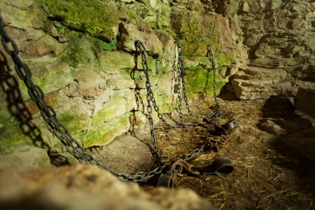 shackles: Castle dungeon prison with chains chain and moss on stone walls Stock Photo