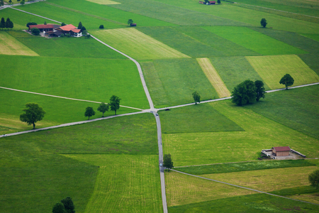 valley view: Areal photograph of read crossing, green fields stripes, trees and houses near Neuschwanstein castle in Germany Stock Photo