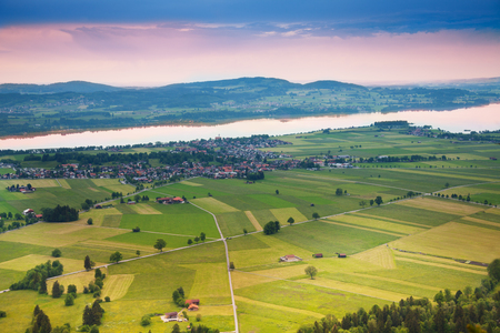 allgau: Areal photograph of read crossing, green fields stripes, trees and houses near Neuschwanstein castle in Germany Stock Photo