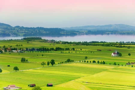 neuschwanstein: Neuschwanstein region areal photograph with fields stripes, roads and Alpsee lake  Stock Photo