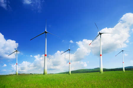 windfarm: Group of five wind turbine spinning and generating electricity on sunny day in the field Stock Photo