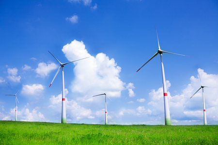 Many wind power electricity turbines turbines on green field on green field on sunny day photo