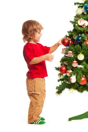 three year old: Happy 3 years old boy decorating Christmas tree, stinging isolated on white