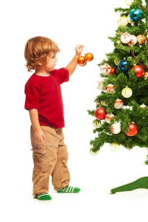decorating christmas tree: Happy 3 years old boy decorating the tree with Christmas balls