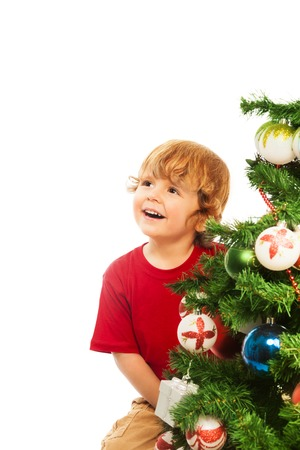 decorating christmas tree: Happy 3 years old boy sitting by the Christmas tree, isolated on whtie Stock Photo