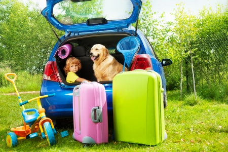 Close shoot of a car with retriever dog and three years old boy waiting in the trunk with bags for trip, trickle, ball, scoop-net photo