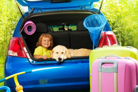 packing: Close shoot of a car with retriever dog and 3 years old boy waiting in the trunk with bags for trip, trickle, ball, scoop-net