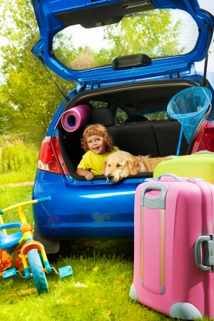 Little three years old boy sitting in the car trunk with a dog waiting for parents to put bags and tricycle for the trip in the car photo