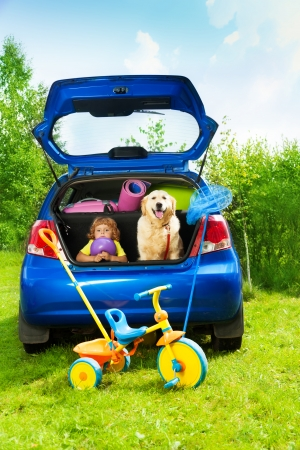 sad dog: Little three years old boy sitting in the car trunk with a dog waiting for parents to put bags and tricycle for the trip in the car