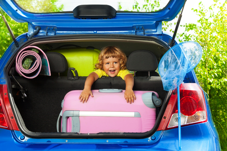 Boy sitting on the back sit with bags and other luggage in the car trunk happy and laughing ready to go on the trip