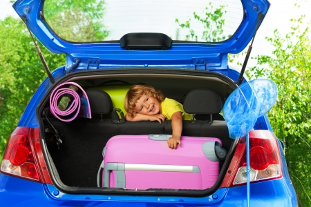 Boy rest on the back sit with bags and other luggage in the car trunk happy and laughing ready to go on the trip