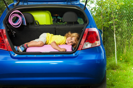 hatchback: Cute little boy laying on the back of the bags and baggage in the car trunk ready to go on vacation with happy expression