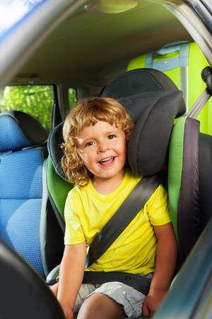 child seat: Little boy sitting on the child seat, happy and laughing on the back of the car Stock Photo