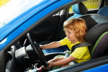 Little boy playing to be a driver in parents car sitting on the first seat steering the wheel photo
