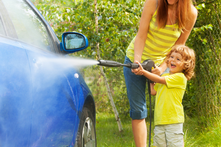 Mother and three years old son washing car with high pressure washer with boy pointing water nozzle  standing in outside in the yeard parking
