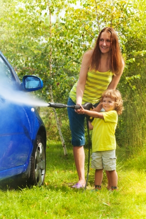 Mother and three years old son washing car with high pressure washer with boy pointing water nozzle
