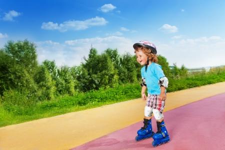 niño en patines: Feliz lindo riendo años thee poco chico patinando patinar cuesta abajo en el parque el día soleado de verano