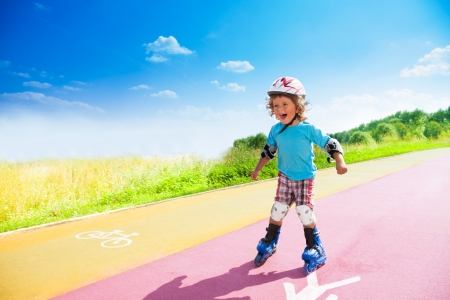 Happy thee years old boy rollerblading in the park on sunny summer day with bike and pedestrian signs on the road