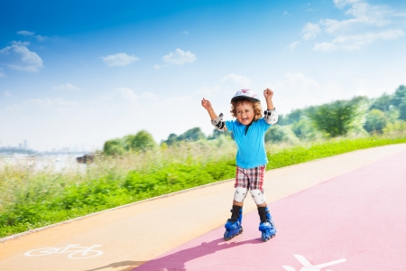 three wheel: Happy thee years old boy rollerblading with lifted hands in the park on sunny summer day with bike and pedestrian signs on the road