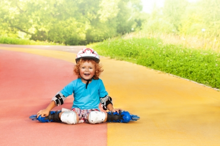 rollerblade: Happy laughing thee years old boy with rollerblades resting sitting on the road in the park on sunny summer day Stock Photo