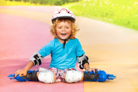 Close portrait of happy laughing thee years old boy with rollerblades resting sitting on the road in the park on sunny summer day photo