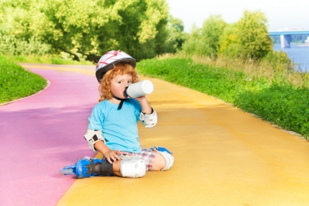 thee: Happy thee years old boy sit with rollerblading and drink water from bottle in the park on sunny summer day