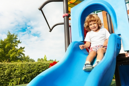 slider: Happy smiling little three years old boy about to slide on blue playground