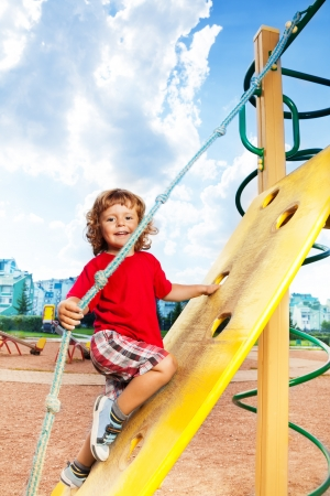 Happy little three years old child on climbing wall holding the rope photo