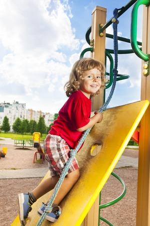 niño trepando: Feliz poco tres años de edad niño chico en la pared de escalada que sostiene la cuerda con una sonrisa en su rostro