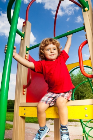 Happy little three years old child boy sitting on playground ready to slide down photo