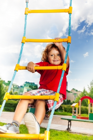 Happy little three years old child boy climbing on the rope ladder with sky on background photo