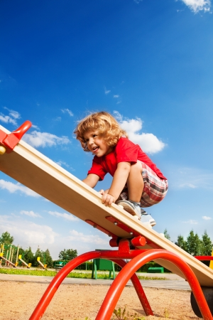 Happy little three years old boy child walking over seesaw keeping balance photo