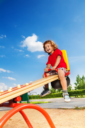 Happy lauging little three years old child sitting on the seesaw photo