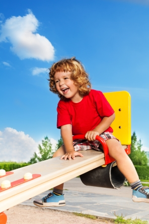 children playground: Happy little three years old child boy sitting and laughing on the seesaw
