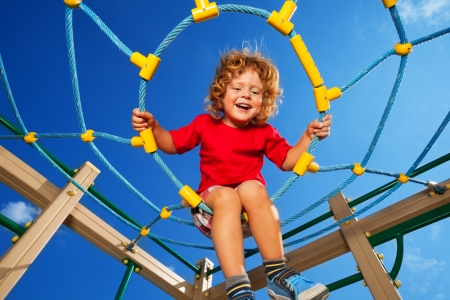 clime: Happy little three years old child clime in the rope web on playground with sky on background