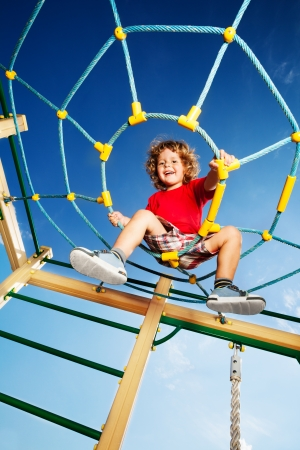 Happy little three years old child boy climbed on top of the rope web on playground looking down and laughing photo