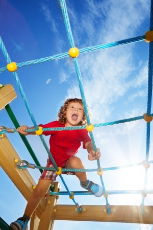 Happy little three years old child with strong roar and scream fun expression climbing on the ropes with sky on background Stock Photo