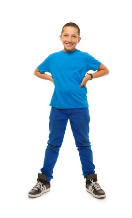 full height: Full height portrait of happy young boy standing isolated on whtie with hand on hips Stock Photo