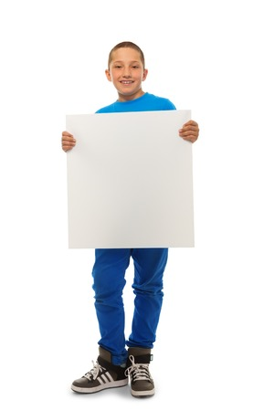 Portrait of happy young boy holding blank sign banner isolated on white photo