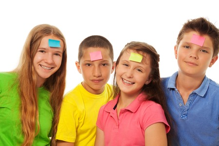 forehead: Group of four kids smiling with color paper sticker on their forehead