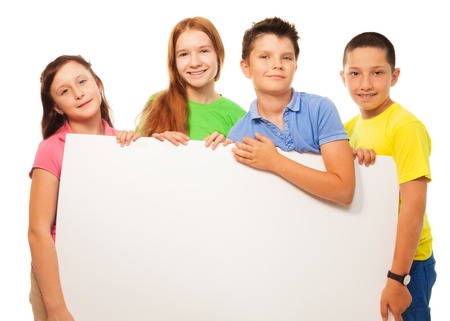 Group of four happy smiling friends, two girls and couple boys, holding blank white sign advertising close portrait photo