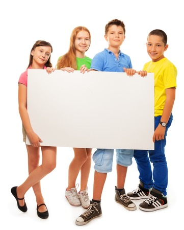Four happy smiling friends, two girls and couple boys, holding blank white sign advertising standing in full height photo