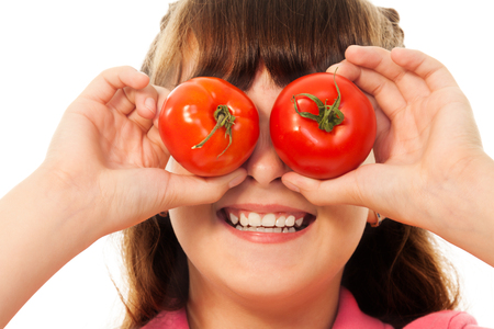 Funny girl holding two tomatoes near eyes and smiling photo
