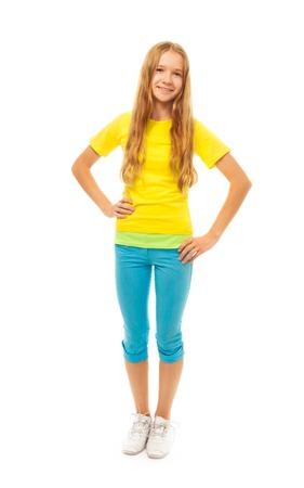 full height: Portrait of happy smiling little school age girl standing isolated on white, full height portrait