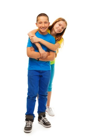Full height portrait of couple of kids hugging together and standing isolated on white Stock Photo - 22511588