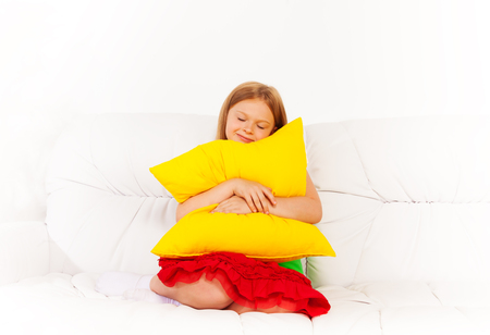 One happy calm sleepy and relaxed girl 6 years old sitting with pillow on the white leather coach Stock Photo - 22511605
