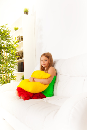 One happy shy little girl years 6 old sitting hugging pillow on the white leather coach in living room at home Stock Photo - 22511606
